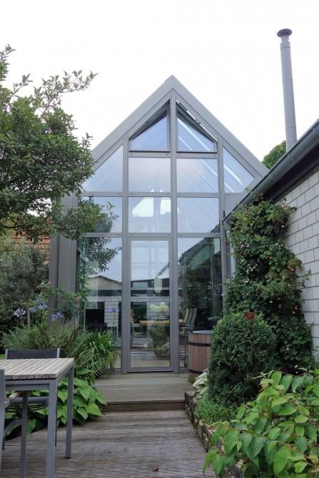 Außenansicht eines Wintergartens: Der Wintergarten besteht aus großen Fenstern mit Aluminium-Rahmen und hat die Dachform eines Satteldaches. Der Wintergarten hat eine Größe von 6,00 x 4,00 Meter und wirkt durch die großen und hohen Fenster sehr groß und hell. Beheizt wird der Wintergarten durch eine Fußbodenheizung und einen eingebauten Kamin. Thermisch getrennte und ausgeschäumte Aluminium-Profile und eine 3-fach Verglasung sorgen für eine optimale Wärmedämmung im Wintergarten. Außerdem ist der Wintergarten mit Hebe-Schiebe-Anlagen, Dreh-Kipp-Türen und Oberlicht-Kipp-Flügel in der Spitze des Satteldaches ausgestattet.