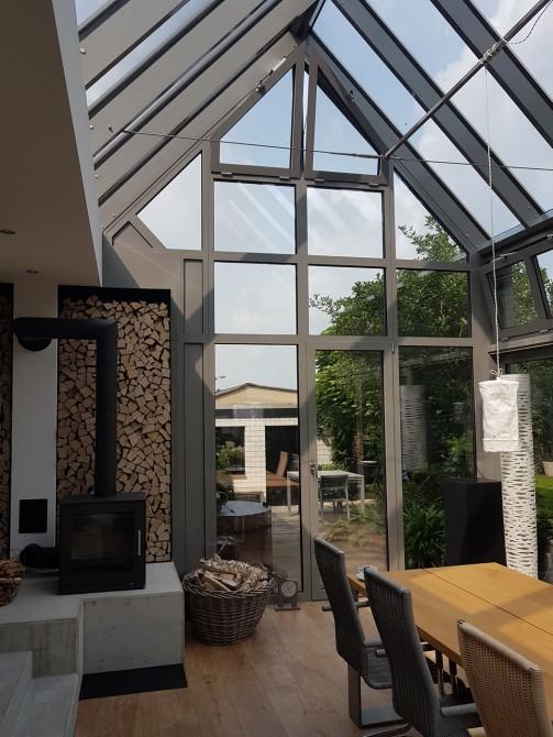 Innenansicht eines Wintergartens mit Satteldach: Der Wintergarten besteht aus einer großen Glasfront und Aluminium-Fensterrahmen in einem modernen Grauton. Die großen Fenster des Wintergartens und des Satteldaches lassen sehr viel Licht in den Raum und lassen den Wintergarten schön hell und offen wirken. Der moderne Holzfußboden und der eingebaute Kamin sorgen für eine sehr gemütliche Atmosphäre im Wintergarten. Außerdem ist der Wintergarten mit Hebe-Schiebe-Anlagen, Dreh-Kipp-Türen und Oberlicht-Kipp-Flügeln ausgestattet. Thermisch getrennte und ausgeschäumte Aluminium-Profile, sowie eine 3-fach Verglasung sorgen für eine optimale Wärmedämmung.