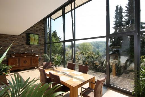 Innenansicht eines 2-geschossigen Wintergartens in Hanglage: Durch die großen Fenster hat man einen herrlichen Blick in die Natur und in die Stadt. Die Fenster sind sehr groß und haben einen Fensterrahmen in der Farbe Anthrazit mit Eisenglimmer. Das Dach des Wintergartens ist in der Form eines Pultdaches und ist mit einer automatisch steuerbaren Dachmarkise ausgestattet. Dreh-Kipp-Türen und Oberlicht-Kipp-Fenster lassen sich individuell anbringen.