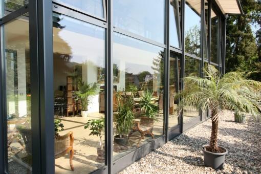Außenansicht eines 2-geschossigen Wintergartens: Die großen Fenster lassen viel Licht in den Wintergarten. Durch die große Aluminium-Glas-Konstruktion sieht der Wintergarten sehr modern aus. Eine Dachmarkise mit automatischer Steuerung ermöglicht eine optimale Regulierung des Lichtes im Wintergarten und bietet Schatten. Die Farbe der Fensterrahmen ist Anthrazit mit Eisenglimmer. Dreh-Kipp-Türen und Oberlicht-Kipp-Fenster lassen sich individuell einbauen. Die Dachform des Wintergartens ist ein Pultdach.