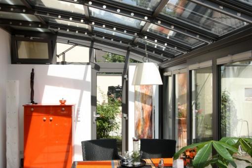 Innenansicht eines Wintergartens mit Bogendach: Der Wintergarten bildet eine ansprechende und hochwertige Wohnraumerweiterung. Das Dach ist in der Form eines Bogendaches gebaut und enthält eine Dachmarkise mit automatischer Steuerung. Außerdem ist der Wintergarten mit Hebe-Schiebe-Anlagen, einer Drehtür und Oberlicht-Kipp-Fenstern ausgestattet.