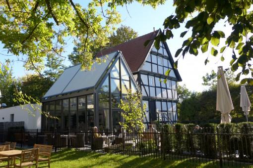 Wintergarten mit großen Fenstern und Satteldach. Der großzügige Wintergarten bietet viel Platz und Licht im Raum. Die Dachmarkise auf dem Satteldach lässt sich automatisch steuern. Außerdem ist der Wintergarten 2-fach verglast und mit einer Fußbodenheizung ausgestattet.