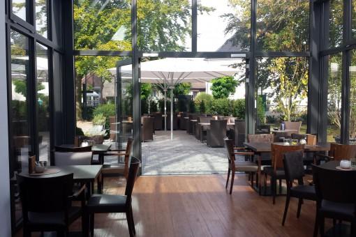 Innenansicht eines Wintergartens: Der offene Wintergarten mit Holzfußboden und großzügigen Fenstern mit Aluminiumrahmen sorgt für eine schöne Atmosphäre. Durch die großen Fenster wirkt der Raum sehr hell und freundlich, da sehr viel Licht in den Raum kommt. Drehtüren lassen sich weit öffnen, sodass ein schöner Übergang von der Terrasse zum Wintergarten entsteht. Die Fenster des Wintergartens sind 2-fach verglast. Eine Fußbodenheizung sorgt für die richtige Wärme im Wintergarten.